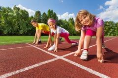 Três crianças de sorriso na posição pronta a correr Foto de Stock