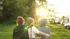 Três crianças, duas meninas e um menino para entrar na distância no parque contra o contexto do por do sol De volta ? escola filme
