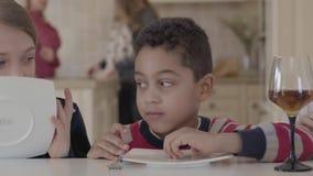 Três crianças engraçadas que sentam-se na tabela com vidros pequenos do bolo e de vinho com suco Duas meninas caucasianos e af video estoque