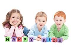 Três crianças felizes com blocos dos miúdos Fotos de Stock Royalty Free