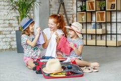 Três crianças felizes das meninas embalam uma mala de viagem em uma viagem Tou do conceito Fotos de Stock Royalty Free