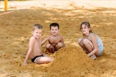 Três crianças felizes nos maiôs constroem uma torre da areia amarela na praia no verão fotografia de stock royalty free