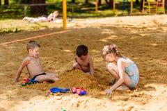 Três crianças felizes nos maiôs jogam com a areia na praia fotos de stock
