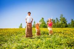 Três crianças felizes que saltam em uns sacos durante o jogo Imagens de Stock