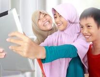 Três crianças muçulmanas que jogam o tablet pc Fotografia de Stock