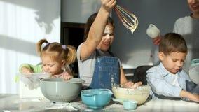 Três crianças na cozinha A menina agita a massa e olha-a fluir da corola A mamã ajuda-os a peneirar vídeos de arquivo