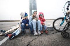 Três crianças patinaram em um skate e em uma bicicleta e sentaram-se para baixo para descansar no freio foto de stock royalty free