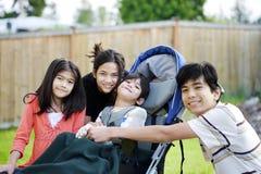 Três crianças pelo irmão incapacitado na cadeira de rodas Imagem de Stock Royalty Free