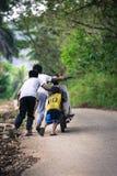 Três crianças que empurram o velomotor subida de inclinação da estrada da vila em leve fotografia de stock royalty free