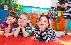 Três crianças que encontram-se no assoalho com mãos sob mordentes imagens de stock