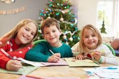 Três crianças que escrevem letras a Santa Together fotos de stock royalty free