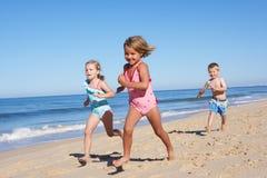 Três crianças que funcionam ao longo da praia imagens de stock