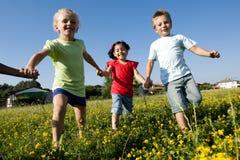 Três crianças que funcionam as mãos da terra arrendada imagem de stock royalty free