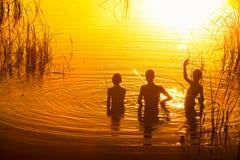 Três crianças que pescam no lago no por do sol foto de stock royalty free