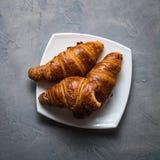 Três croissant e um mordidos em uns pires brancos em um fundo concreto cinzento Foto de Stock
