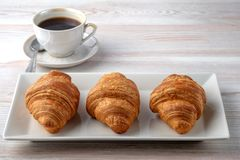 Três croissant em uma placa retangular fotos de stock royalty free
