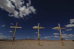 Três cruzes de madeira no deserto com céu azul Imagem de Stock