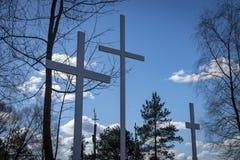 Três cruzes nas árvores contra um céu azul nebuloso fotografia de stock royalty free
