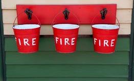 Três cubetas de incêndio vermelho Fotografia de Stock Royalty Free