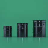 Três cubetas pretas em uma opinião dianteira do fundo verde Imagem de Stock Royalty Free