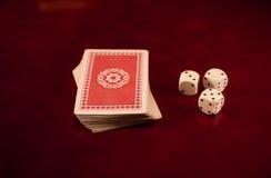Três cubos dos dados e plataformas de cartões na obscuridade que reflete a fortuna de madeira do casino dos jogos do fundo Fotografia de Stock