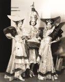 Três dançarinos em vestidos longos e em grandes chapéus Imagens de Stock Royalty Free