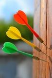 Três dardos na placa de madeira Imagens de Stock