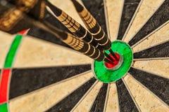 Três dardos no fim do bullseye acima Fotografia de Stock Royalty Free