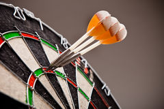 Três dardos que batem a contagem 180 perfeita na placa de dardo Imagem de Stock Royalty Free