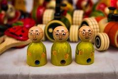 Três de madeira boneca calva vestida amarela com espetáculos Modelo de Gandhi imagens de stock