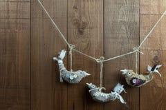 Três decorações feitos a mão do pássaro da tela em um fundo de madeira Fotografia de Stock Royalty Free