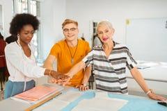 Três desenhadores de moda felizes modernos que mostram o espírito de equipe fotografia de stock royalty free