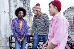 Três desenhistas novos à moda que têm a conversação no balcão imagem de stock