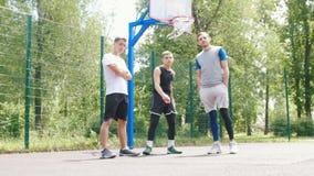 Três desportistas consideráveis que ficam no ar livre do campo de básquete - um desportista que faz keepy-uppies video estoque