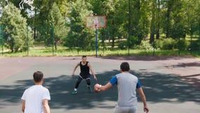 Três desportistas que jogam o basquetebol no ar livre da corte - homem no uniforme preto que joga a bola video estoque