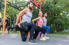 Três determinaram os amigos que fazem esticando exercícios para os pés como imagem de stock
