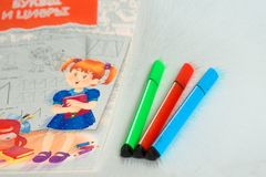 Três do marcador que encontra-se ao lado de um caderno para alunos, colorindo Figuras dos povos da ilustração imagens de stock