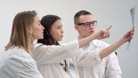 Três doutores novos que olham o raio X da espinha foto de stock