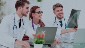 Três doutores que olham atentamente no raio X e que discutem o imagens de stock