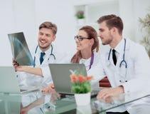 Três doutores que olham atentamente no raio X e que discutem o fotografia de stock royalty free