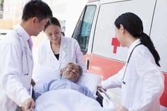 Três doutores que rodam em um paciente idoso em uma maca na frente de uma ambulância Fotografia de Stock Royalty Free