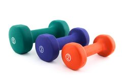 Três dumbbells coloridos do tamanho diferente Foto de Stock Royalty Free