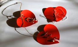 Três emendaram corações vermelhos Conceito do coração quebrado imagem de stock royalty free