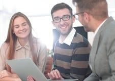 Três empregados felizes que trabalham na linha com uma tabuleta imagem de stock