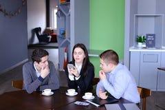 Três empregados ocupados da empresa, dois homens novos e mulher ocupados com Fotos de Stock Royalty Free