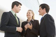 Três empresários que estão ao ar livre pelo edifício Fotos de Stock Royalty Free