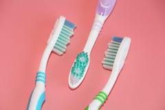 Três escovas de dentes em um fundo cor-de-rosa Higiene oral foto de stock