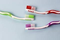 Três escovas de dentes multi-coloridas em um fundo azul, close-up, dentes importam-se o conceito, espaço da cópia foto de stock royalty free