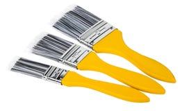 Três escovas de pintura de tamanhos diferentes com punho amarelo Imagens de Stock Royalty Free