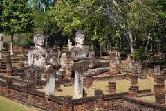Três esculturas antigas da Buda nas ruínas do templo Wat Phra Kaeo Dia ensolarado Kamphaeng Phet, Tailândia Imagens de Stock Royalty Free